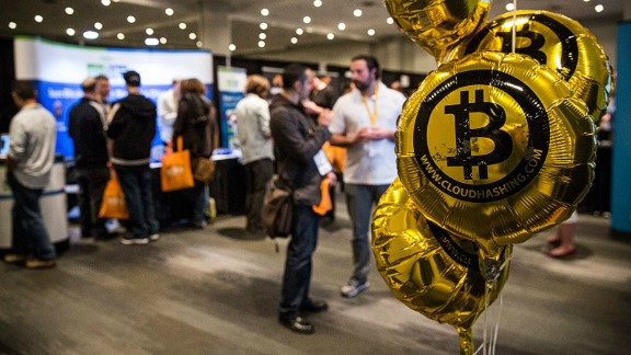 Its value fluctuates and is not regulated, although payment companies that trade with Bitcoin tend to fall under the same regulations as conventional money transfer services. Pictured: People attend a Bitcoin conference in New York in 2014.