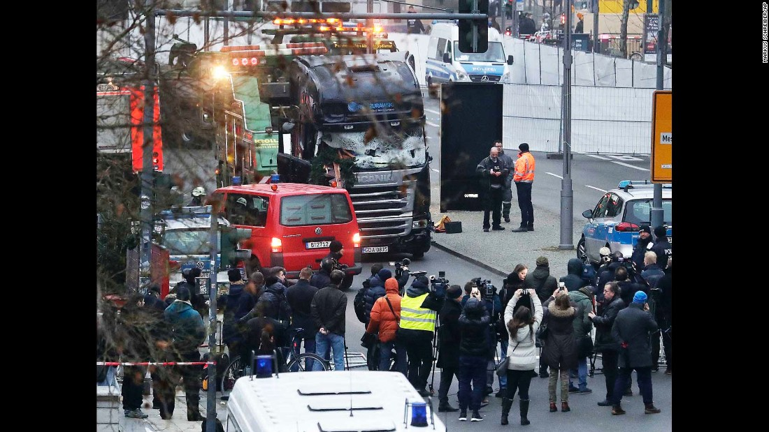 Members of the press crowd around the crash site on December 20.