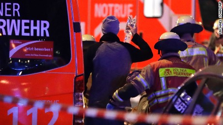 Firefighters attend an injured person after a truck ran into crowded Christmas market in Berlin, Germany, Monday, Dec. 19, 2016. Police said that several people have been killed. (AP Photo/Michael Sohn)