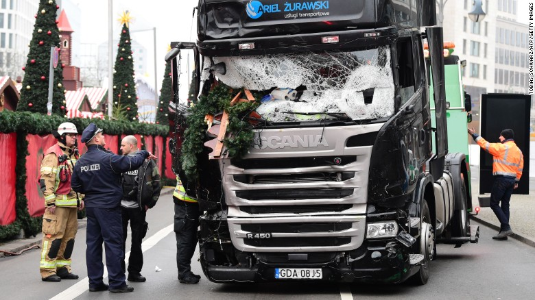 "A policeman and firemen stand next to a truck on December 20, 2016 at the scene where it crashed into a Christmas market near the Kaiser-Wilhelm-Gedaechtniskirche (Kaiser Wilhelm Memorial Church) in Berlin. German police said they were treating as ""a probable terrorist attack"" the killing of 12 people when the speeding lorry cut a bloody swath through the packed Berlin Christmas market."