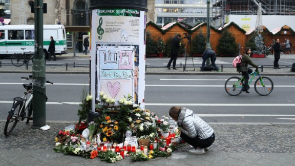 A woman lays flowers at a makeshift memorial across from the market.