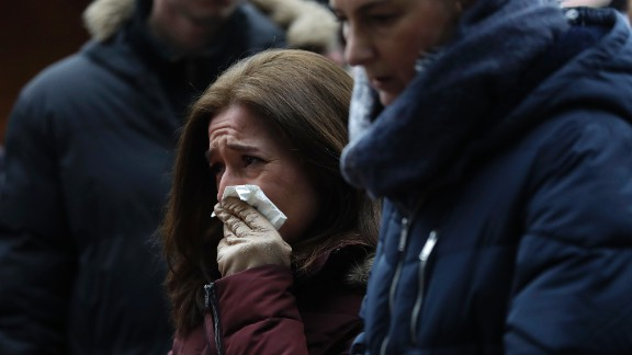 A woman reacts near the crime scene on December 20.