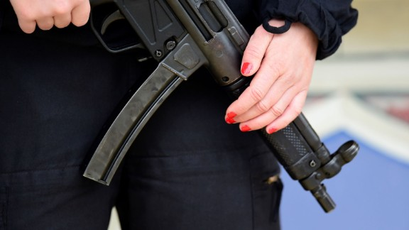 A police officer holds her weapon near the market.