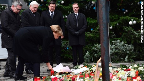 TOPSHOT - German Chancellor Angela Merkel (foreground), German Interior Minister Thomas de Maiziere (L) and German Foreign Minister Frank-Walter Steinmeier (2nd L) stand at a makeshift memorial for the victims of an attack on December 20, 2016 in front of the Kaiser-Wilhelm-Gedaechtniskirche (Kaiser Wilhelm Memorial Church) in Berlin, where a truck crashed into a Christmas market. Twelve people were killed and almost 50 wounded, 18 seriously, when the lorry tore through the crowd on December 19, 2016, smashing wooden stalls and crushing victims, in scenes reminiscent of July's deadly attack in the French Riviera city of Nice. / AFP PHOTO / Tobias SCHWARZTOBIAS SCHWARZ/AFP/Getty Images
