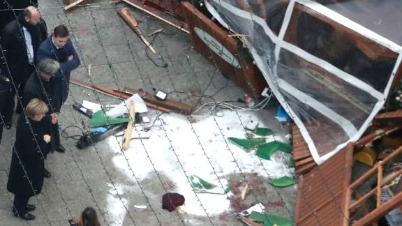 Merkel, bottom left, views the scene of the attack.