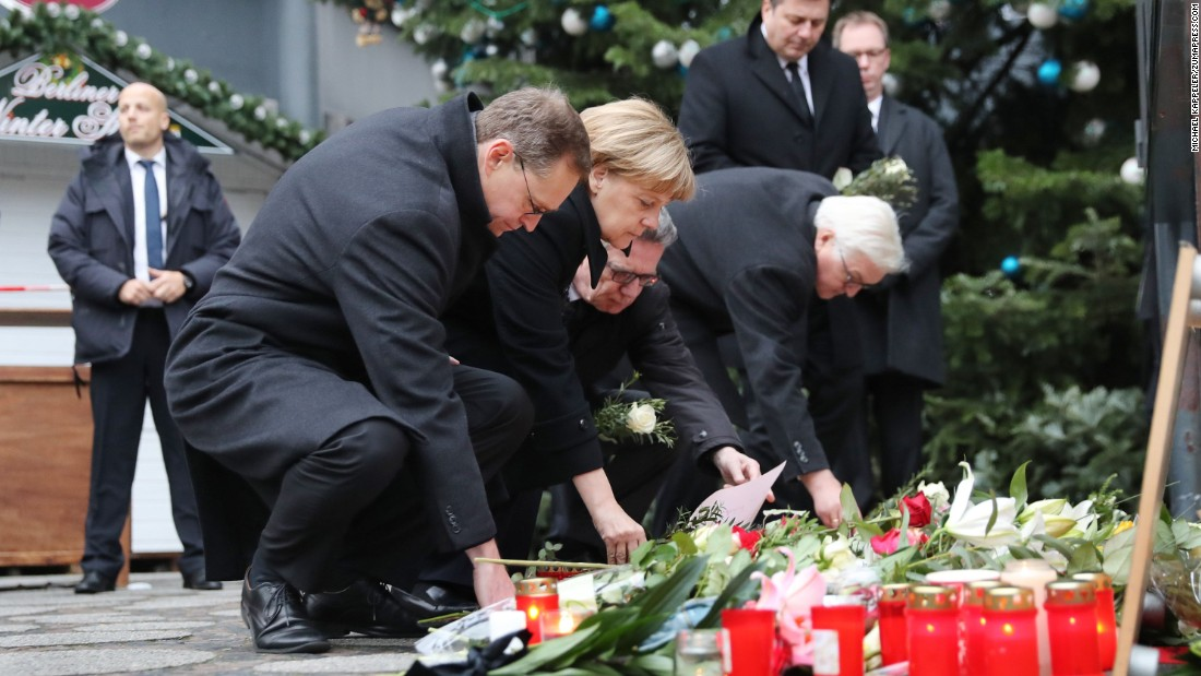 German Chancellor Angela Merkel lays flowers at the memorial on December 20. She is joined by, from left, Berlin Mayor Michael Muller, Minister of the Interior Thomas de Maiziere and Foreign Minister Frank-Walter Steinmeier.