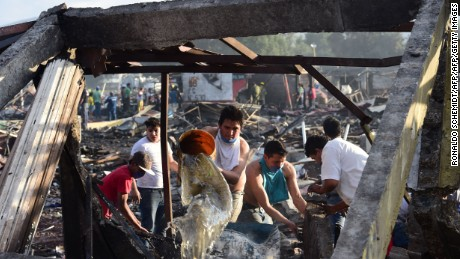 People put out smoldering embers and search amid the debris left by a huge blast that occured in a fireworks market in Mexico City, on December 20, 2016 killing at least 26 people and injuring scores. The conflagration, in the suburb of Tultepec, set off a quickfire series of multicolored blasts and a vast amount of smoke that hung over Mexico City.  / AFP / RONALDO SCHEMIDT        (Photo credit should read RONALDO SCHEMIDT/AFP/Getty Images)