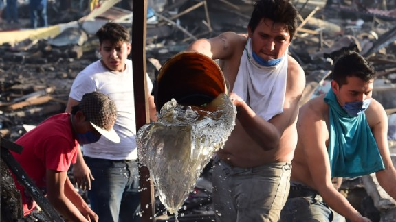 People work to extinguish embers still burning in the debris from the explosion.