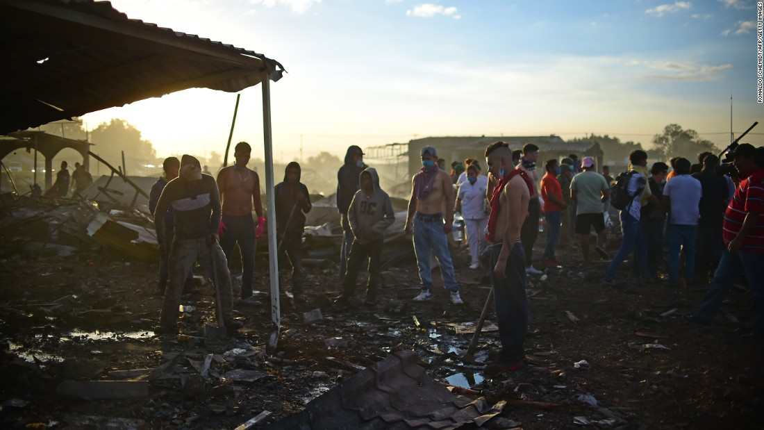 Rescuers and survivors gather amid the destroyed market.