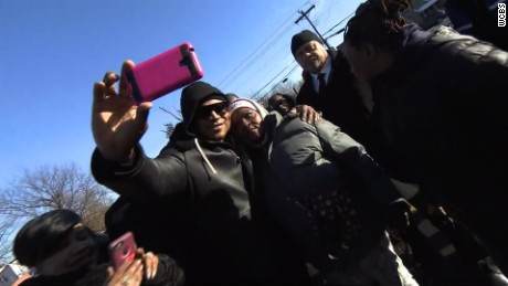 LL Cool J takes selfies with residents in the neighborhood where he grew up.