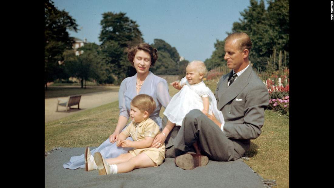 Princess Elizabeth and her husband, Prince Philip, sit on a lawn with their children Prince Charles and Princess Anne in August 1951.