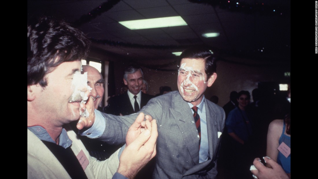 Prince Charles shares a playful pie in the face while visiting a community center in Manchester, England, in December 1983.
