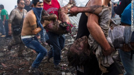 TOPSHOT - Victims severely burned are taken away by rescuers from the smoldering ruins of a fireworks market, flattened by a huge blast that killed at least 26 and injured dozens, in Mexico City, on December 20, 2016.  The conflagration, in the suburb of Tultepec, set off a quickfire series of multicolored blasts and a vast amount of smoke that hung over Mexico City.  / AFP / ISRAEL GUTIERREZ / GRAPHIC CONTENT        (Photo credit should read ISRAEL GUTIERREZ/AFP/Getty Images)