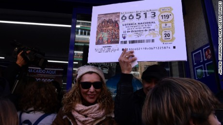 A man brandishes a giant copy of the Spanish Christmas lottery first prize outside the Spanish Administration Lottery where it was sold in the Embajadores neighbourhood in Madrid, on December 22, 2016. The Gordo (Fat One) lottery first took place in 1812 in Cadiz and has not missed a year since, continuing through Spains civil war between 1936 and 1939. In 1938, there were actually two Christmas lotteries, one held in Burgos by dictator General Francos Nationalist regime, and the other in Republican-ruled Barcelona. / AFP / JAVIER SORIANO        (Photo credit should read JAVIER SORIANO/AFP/Getty Images)