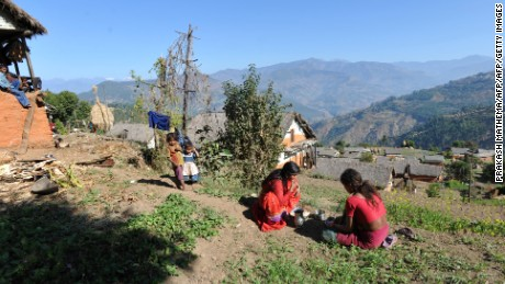 TO GO WITH Nepal-women-religion-society-chhaupadi,FEATURE by Frankie Taggart Nepalese villager Chandrakal Nepali (C) eats as children look on in the village of Achham, some 800kms west of Kathmandu on November 23, 2011.  Isolation is part of a centuries-old Hindu ritual known as chhaupadi which is blamed for prolongued depression, young women's deaths and high infant mortality rates in remote, impoverished western Nepal. Under the practice women are prohibited from participating in normal family activities during menstruation and after childbirth.     AFP PHOTO/Prakash MATHEMA (Photo credit should read PRAKASH MATHEMA/AFP/Getty Images)