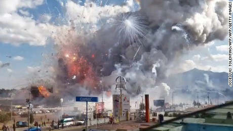 TOPSHOT - A massive explosion guts Mexico's biggest fireworks market in Tultepec, on December 20, 2016. The explosion killed at least 31 people and injured 72, authorities said. The conflagration in the Mexico City suburb of Tultepec set off a quick-fire series of multicolored blasts that sent a vast cloud of smoke billowing over the capital. / AFP / Jose Luis TOLENTINO        (Photo credit should read JOSE LUIS TOLENTINO/AFP/Getty Images)