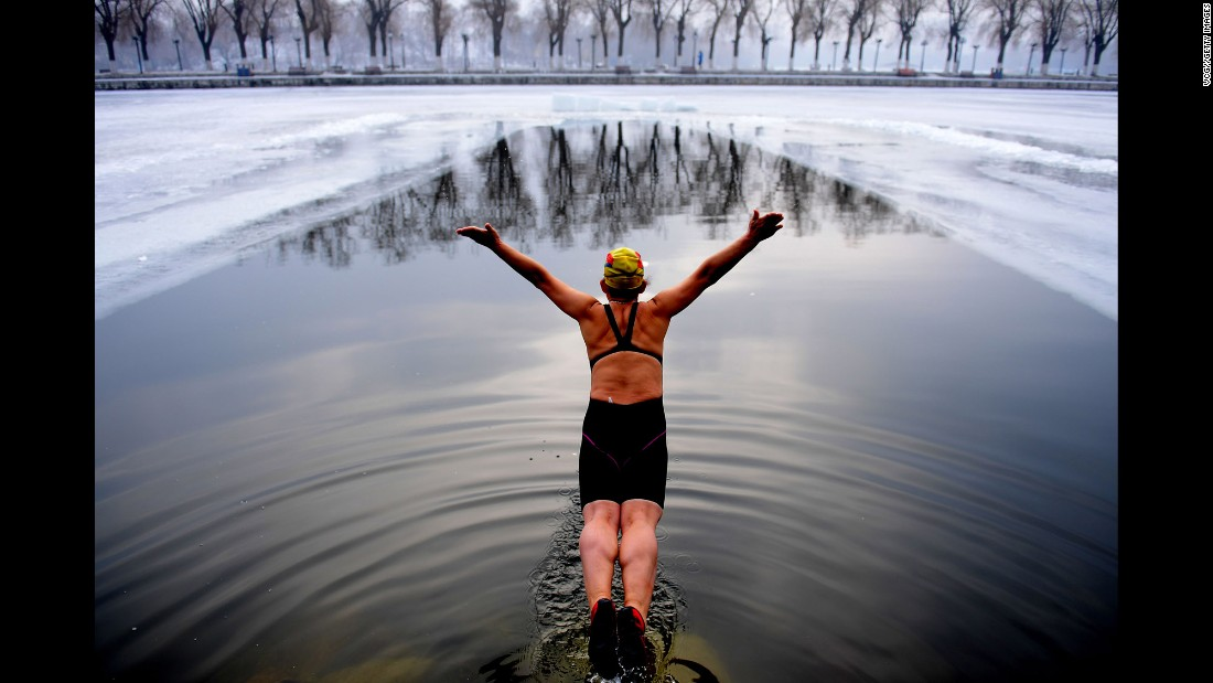 A swimmer jumps into an icy river in Shenyang, China, on Tuesday, December 20.