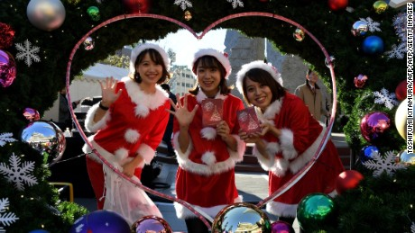 Wearing Santa Claus costumes, employees of a toy maker pose in an event underneath the landmark Tokyo Sky Tree in Tokyo on December 10, 2016.   The Japan Toy Association, consisting of 211 toy companies, held the Christmas event to attract toy as gift on the Christmas day. / AFP / TOSHIFUMI KITAMURA        (Photo credit should read TOSHIFUMI KITAMURA/AFP/Getty Images)