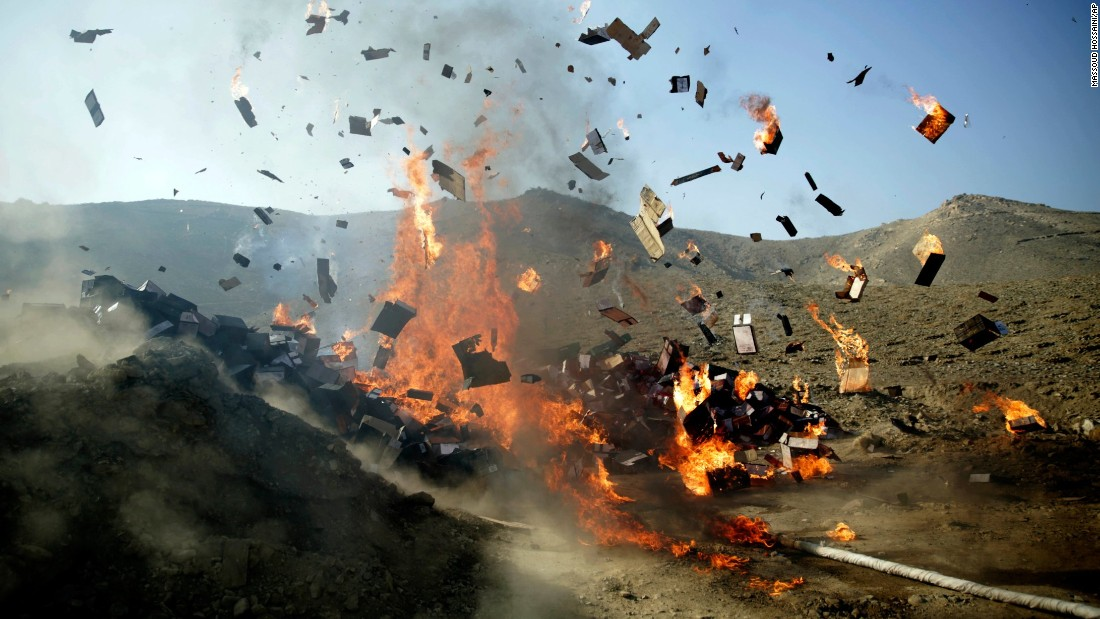 Alcoholic drinks burn during a ceremony near Kabul, Afghanistan, on Tuesday, December 20. Afghan officials burned 98 tons of opium, heroin, hashish and alcoholic drinks.