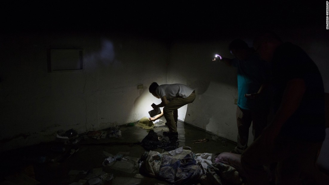 A Chinese national, living in Venezuela, looks for his passport in the remains of the building where he maintains a home and business in Ciudad Bolivar on Monday, December 19. Hundreds of police and soldiers were deployed to Ciudad Bolivar, where dozens of businesses were destroyed or damaged after massive looting.
