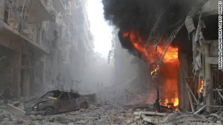 Debris cover a street and flames rise from a building following a reported air strike by Syrian government forces on March 7, 2014 during the Friday prayer in the Sukkari neighborhood of the northern city of Aleppo. More than 140,000 people have been killed in Syria since the start of a March 2011 uprising against the Assad family's 40-year rule. AFP PHOTO / BARAA AL-HALABI        (Photo credit should read BARAA AL-HALABI/AFP/Getty Images)