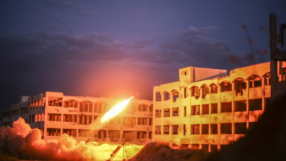 A Syrian opposition tank fires a rocket toward an Assad forces' building during clashes near the Air Intelligence building of Jamiat al-Zahra, Aleppo, on April 13, 2015.