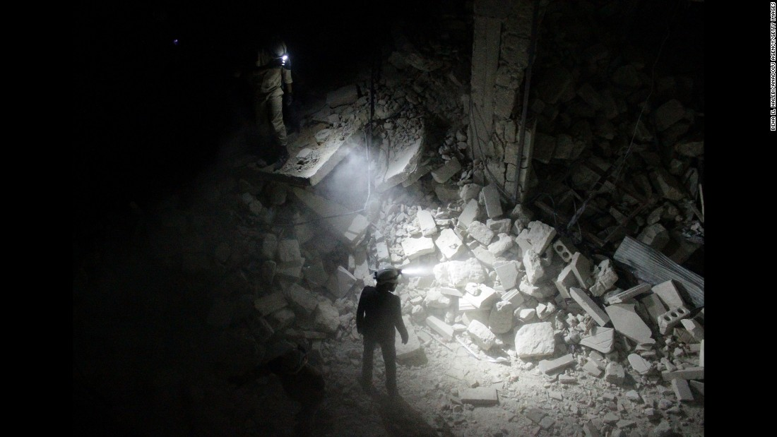 Search and rescue team members inspect collapsed buildings after Assad regime forces attacked residential areas in the Karm al-Beik region of Aleppo on July 9, 2015.