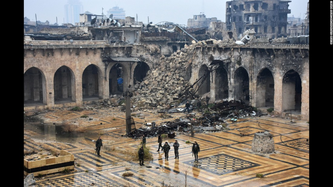 Syrian pro-government forces walk in the damaged ancient Umayyad Mosque in the old city of Aleppo on December 13, 2016, after they captured the area.