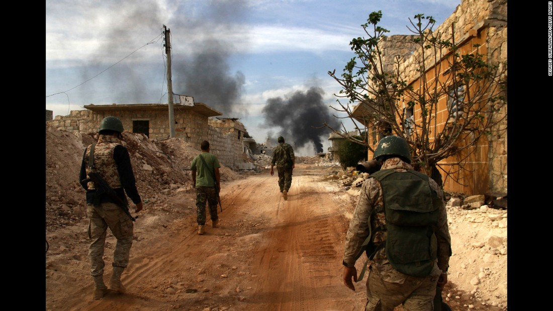 Syrian government forces walk in the strategic area of the Bazo hilltop, on the southern outskirts of Aleppo, as they advance to seize the rebel-held eastern part of the city on October 25, 2016.