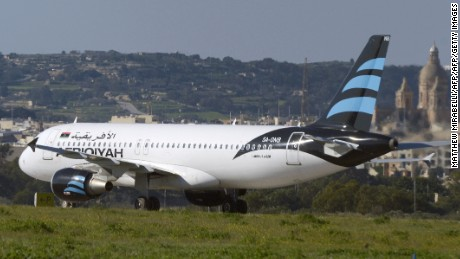 A picture taken on December 23, 2016 shows a hijacked Airbus A320 operated by Afriqiyah Airways after it landed at Luqa Airport, in Malta. A hijacked plane from Libya landed on the Mediterranean island of Malta on December 23 with 118 people including seven crew members on board, Malta's prime minister and government sources said. The Airbus A320 had been on a domestic Libyan route operated by Afriqiyah Airways from Sabha in the south to the capital Tripoli but was re-routed.  / AFP / Matthew Mirabelli / Malta OUT        (Photo credit should read MATTHEW MIRABELLI/AFP/Getty Images)