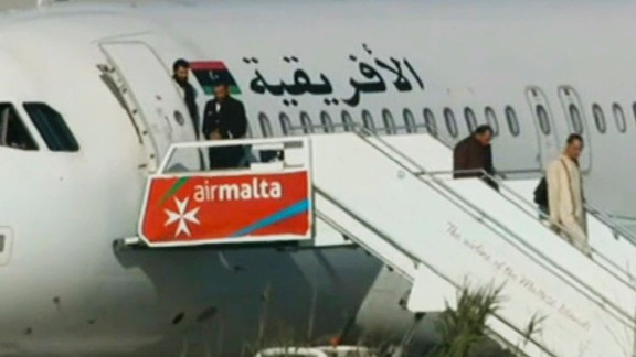 An Afriqiyah Airways plane stands on the tarmac at Malta's Luqa International airport as passengers depart, Friday, Dec. 23, 2016. Hijackers diverted the Libyan commercial plane to Malta on Friday and threatened to blow it up with hand grenades, Maltese authorities and state media said. (AP Photo)