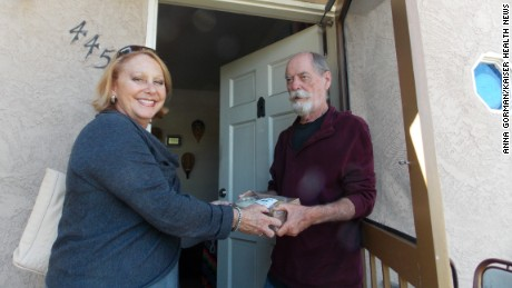 Debbie Case, CEO of the Meals on Wheels San Diego County, delivers lunch and dinner to 75-year-old David Kelly. Kelly lost his sight about two years ago and reluctantly gave up cooking. (Anna Gorman/KHN)