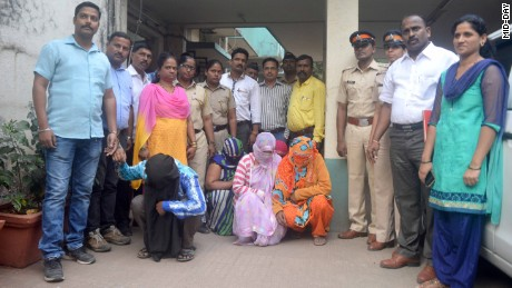 Police stand with the members of an alleged child trafficking gang in Mumbai.
