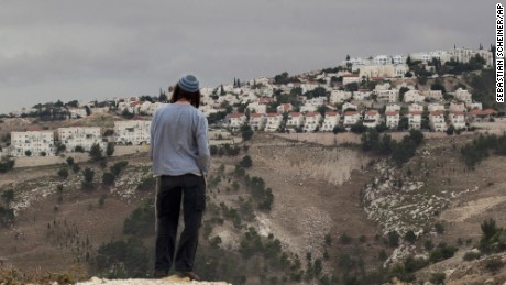"FILE - in this Wednesday, Dec. 5, 2012 file photo, A Jewish settler looks at the West bank settlement of Maaleh Adumim, from the E-1 area on the eastern outskirts of Jerusalem. In his landmark speech to the Arab world seven years ago, President Barack Obama warned that Israeli settlements on occupied territories were undermining hopes for peace. ""It is time for these settlements to stop,"" he declared. As Obama heads into the home stretch of his presidency, he leaves behind an unfulfilled vision.(AP Photo/Sebastian Scheiner, File)"