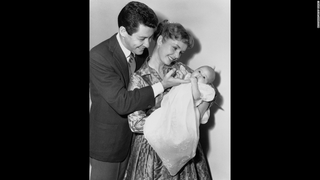 Fisher was born in Beverly Hills on October 21, 1956, to Eddie Fisher and Debbie Reynolds. Here, they gaze proudly at their newborn daughter on January 2, 1957.