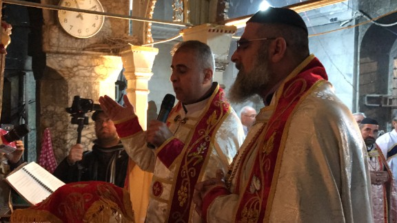 Father Behnam Lalo, left, and another clergyman pray during Christmas Mass held in Bartella.