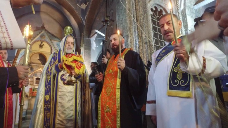 Clergymen hold Mass on Christmas Eve for people who returned to Bartella, Iraq, after ISIS militants had been driven out of the town.