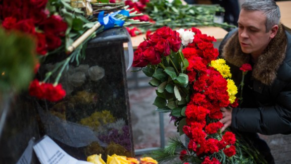 """A man places flowers outside the building of the Alexandrov Ensemble in Moscow on Sunday. Alexander Kibovsky, head of Moscow's culture department, called them """"our cultural paratroopers."""""""