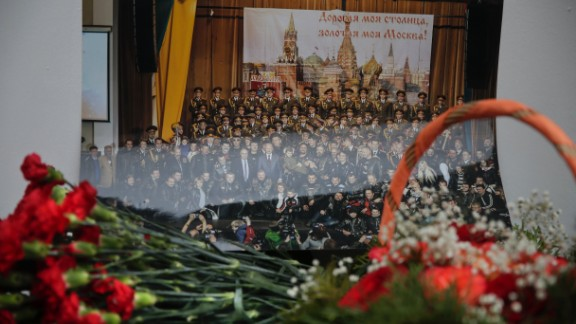 Flowers lay in front of a photo of the Alexandrov Ensemble at the group
