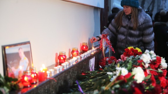 A woman lights a candle at a memorial in Moscow.