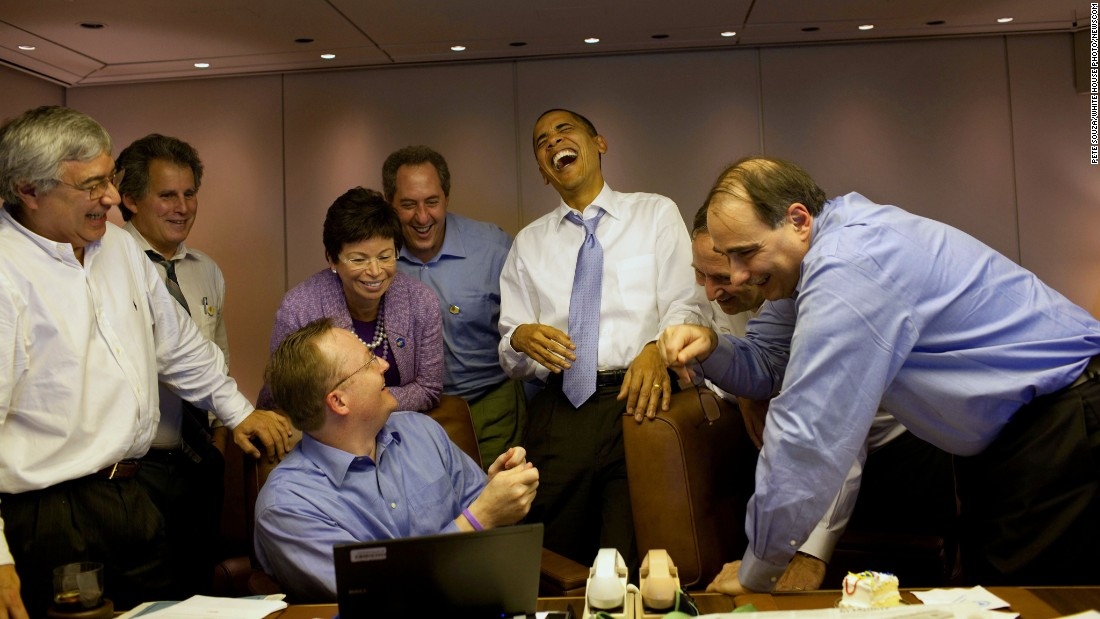 Obama laughs with aides aboard Air Force One in November 2009.