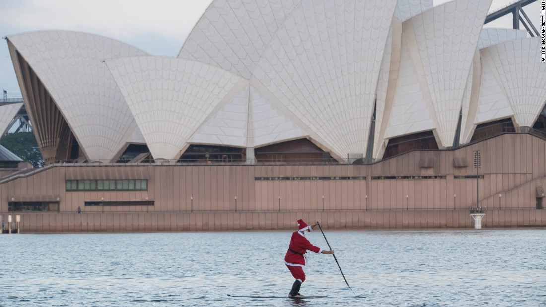 A Man Wearing A Santa Outfit Paddleboards In Sydney Harbour On Christmas Day In Australia