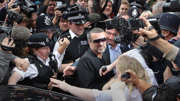 Singer George Michael, center, is surrounded by press and police on August 24, 2010 in London, after leaving a courthouse. Michael pleaded guilty to driving under the influence of drugs and possessing cannabis after he crashed his car into a photo processing shop in London the month before.