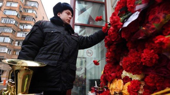 A Russian police orchestra musician places a flower in tribute to members of the Alexandrov Ensemble outside their home stage building in Moscow on December 26. The popular ensemble was scheduled to perform for Russian pilots in Syria ahead of New Year