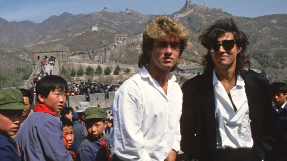"""CHINA - 1985/04/07: Young children sporting """"Mao"""" jackets and caps gape at George Michael (left) and Andrew Ridgeley, of the pop group Wham who are visiting the Great Wall as they promote the first-ever gig by a Western pop band in communist China.  Wham played a concert at Beijing's People's Stadium, thereby becoming a milestone not only in pop but also in Chinese history, even if most Chinese hadn't a clue who they were and even fewer actually got to see them in action.. (Photo by Peter Charlesworth/LightRocket via Getty Images)"""