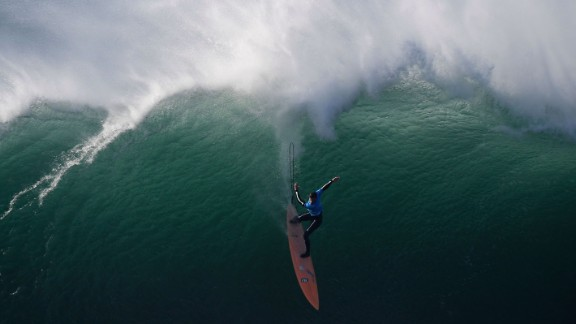 TOPSHOT - American big wave surfer Nic Lamb drops a wave off Praia do Norte in Nazare  during the first edition of the World Surf League
