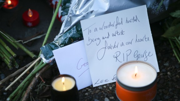 Messages and candles are seen among floral tributes outside the singer