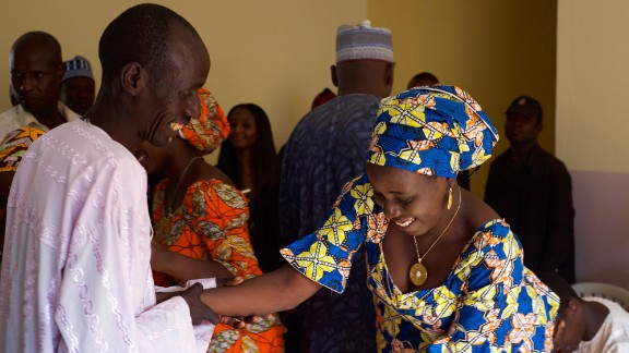 A father greets his daughter after she arrived with 20 other freed Chibok girls.