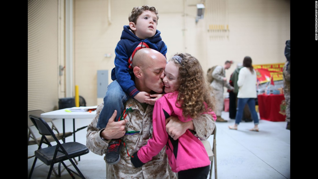 US Marine Branden Palmer kisses his daughter Abigail while his son Declan sits on his shoulders during a homecoming visit in Oceanside, California, on Friday, December 16.
