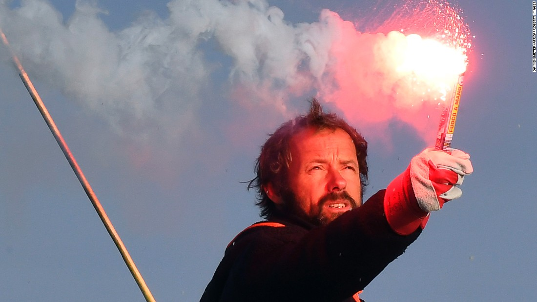 "Thomas Coville holds a burning flare onboard his ""Sodebo Ultim'"" multihull as he arrives in the port of Brest, western France, on December 26, 2016, after beating the record in solo nonstop, round-the-world sailing."